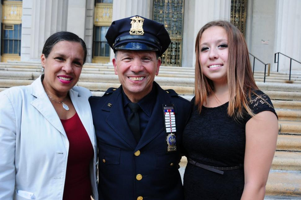 Bronx Supreme Court Officer David Fliegelman, center, with his wife Elix, left, and daughter Dakota, is all smiles during his last day on the job.
